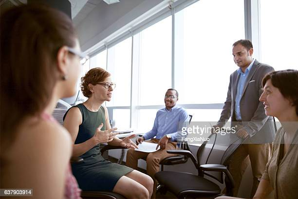 Mature woman talking with business colleagues in office