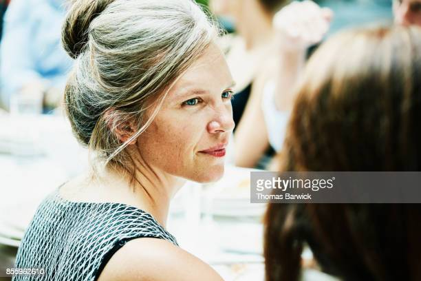 Mature woman talking with friend during celebration dinner
