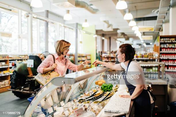 mature woman tasting cheese sample at delicatessen - delicatessen stock pictures, royalty-free photos & images