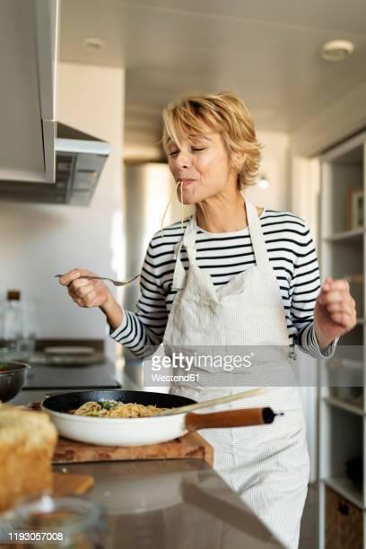 mature woman tasting homemade pasta dish in kitchen at home - kochen stock-fotos und bilder