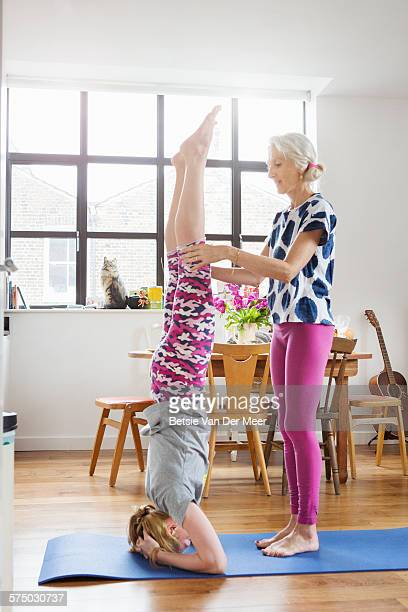Mature woman teaches daughter yoga headstand