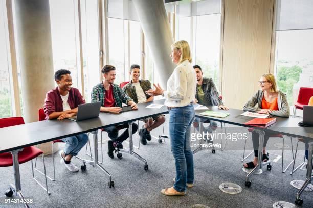 Mogen kvinna undervisa klass av högskolestudenter i modern byggnad