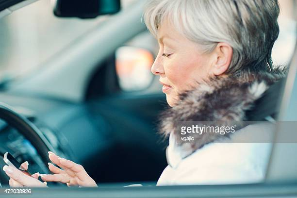 Mature Woman Texting in a car.
