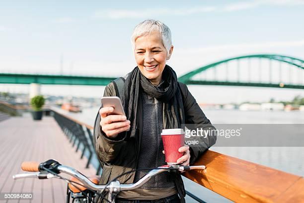 Mujer madura enviando mensajes de texto en su teléfono inteligente y bebiendo café
