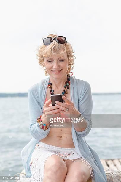 Mature woman texting on smarthphone