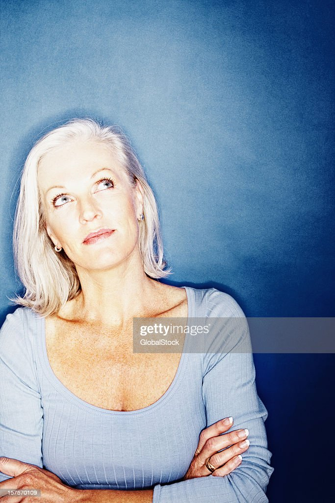 Mature woman thinking against blue background : Stock Photo