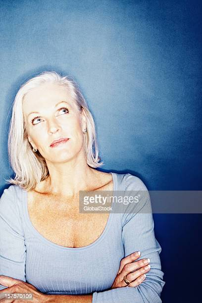 Mature woman thinking against blue background