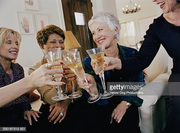 Mature woman toasting drinks, smiling