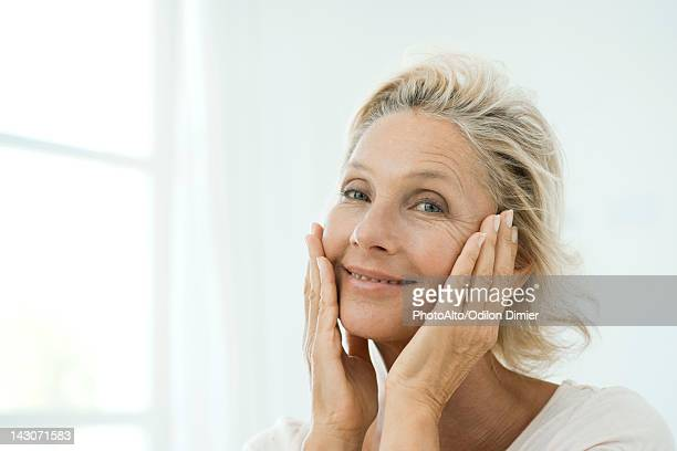 mature woman touching cheeks, smiling, portrait - wrinkled stock pictures, royalty-free photos & images