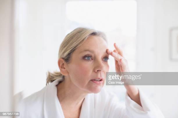 Mature woman touching eyebrow at bathroom mirror