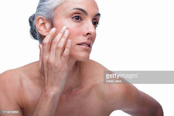 Mature woman touching face