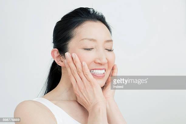 mature woman touching face - 美容 ストックフォトと画像