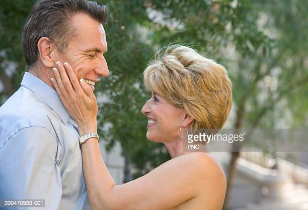 Mature woman touching mature man's cheek, smiling, side view