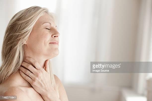 madura mulher tocando seu pescoço - mulheres maduras - fotografias e filmes do acervo