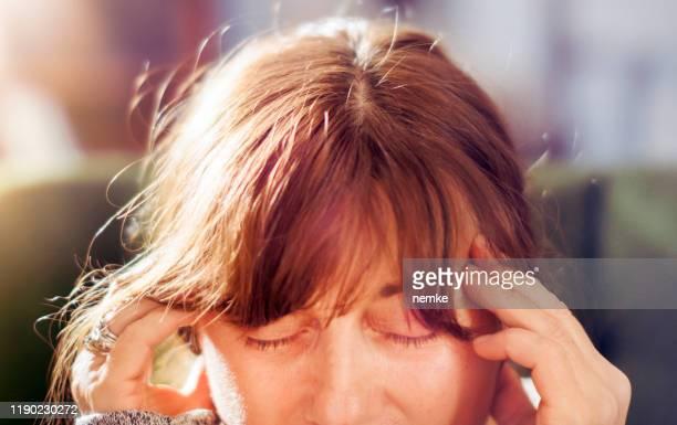 mulher madura que toca em templos, conceito da enxaqueca - meningite - fotografias e filmes do acervo