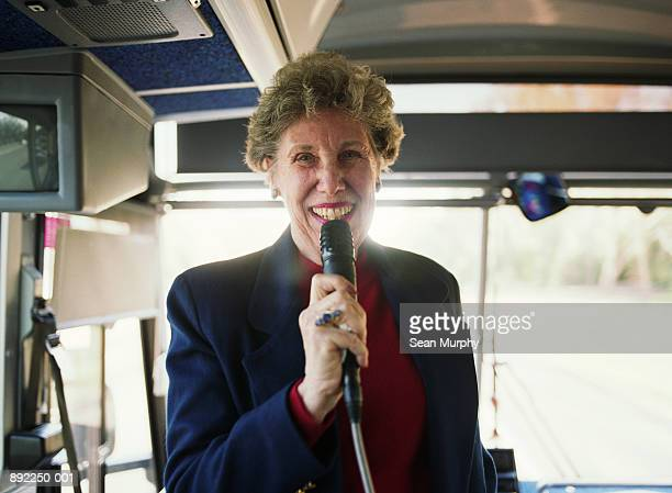 mature woman tour guide holding microphone on bus, smiling - ツアーガイド ストックフォトと画像