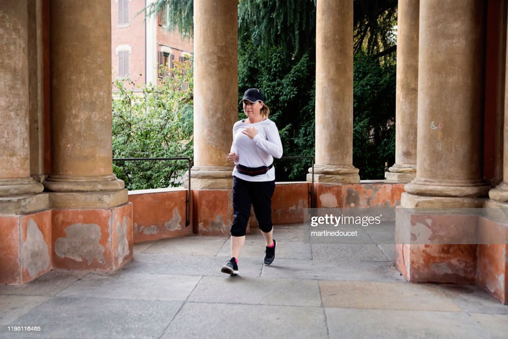 Mature woman training outdoors in city. : Stock Photo