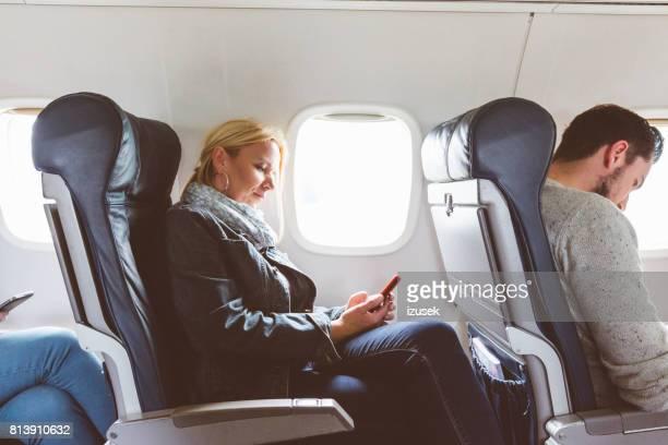 Reife Frau, die Reisen mit dem Flugzeug mit Handy