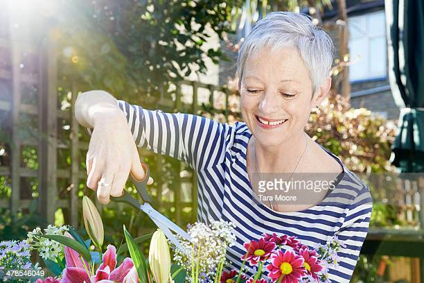 mature woman trimming flowers in garden