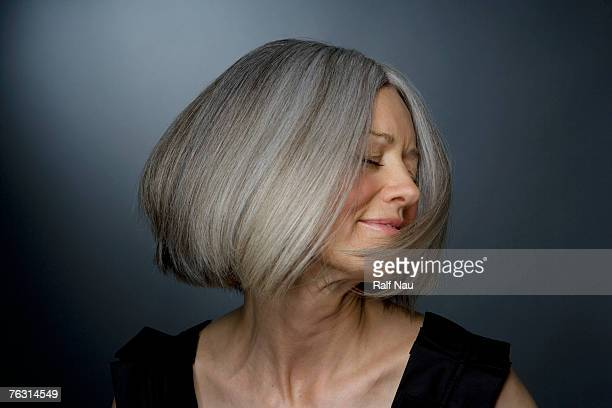 mature woman turning head, eyes closed, close-up - graues haar stock-fotos und bilder