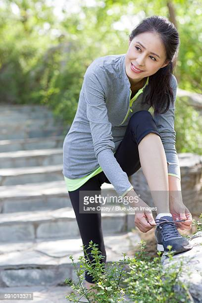 mature woman tying her shoelaces - lace fastener stock pictures, royalty-free photos & images