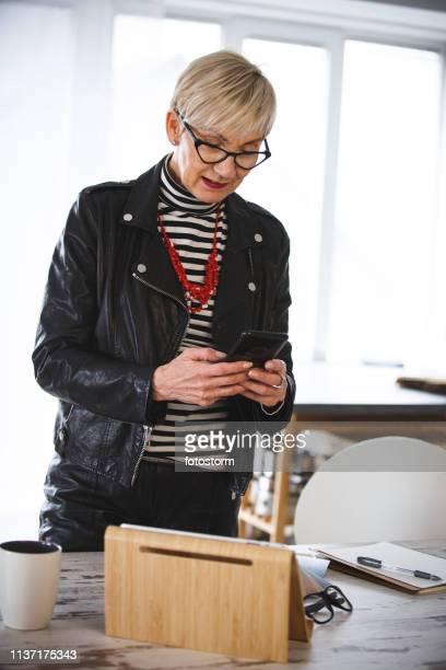 rijpe vrouw te typen op de mobiele telefoon in haar kantoor - werkneemster stockfoto's en -beelden