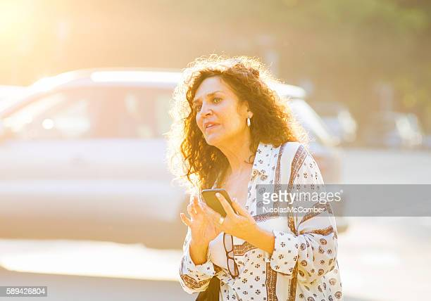 Mature woman uses smart phone to call shared ride