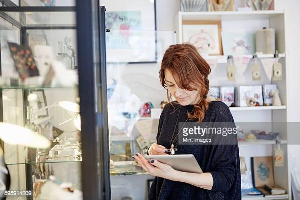 a mature woman using a digital tablet, using the touch screen, stock-taking in a small gift shop.  - onafhankelijkheid stockfoto's en -beelden