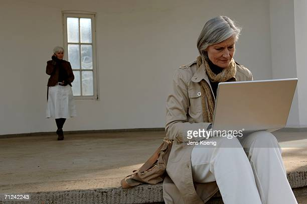 mature woman using a laptop, a second woman using a mobile phone in background - older women in short skirts stock pictures, royalty-free photos & images