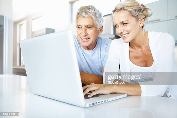 Mature woman using a laptop in the kitchen