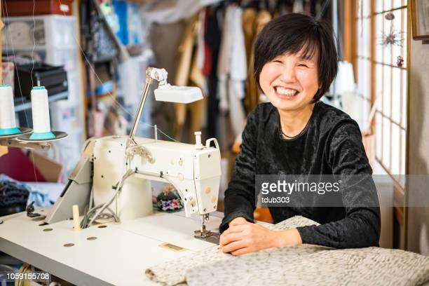 彼女の小さな繊維のスタジオでミシンを使って熟女 - ワーキングシニア ストックフォトと画像