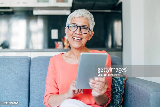 mature woman using digital table - white hair stock pictures, royalty-free photos & images
