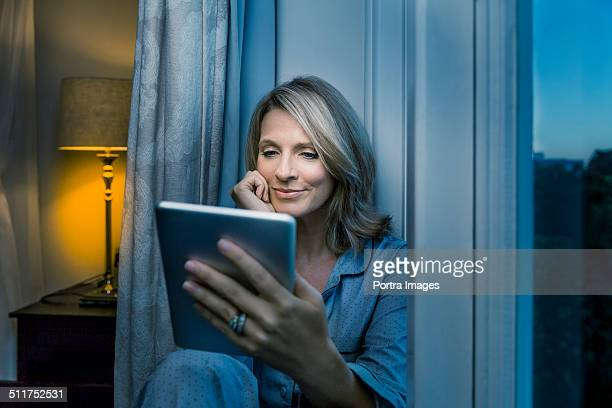 Mature woman using digital tablet at home
