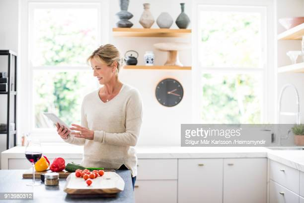 Mature woman using digital tablet in kitchen