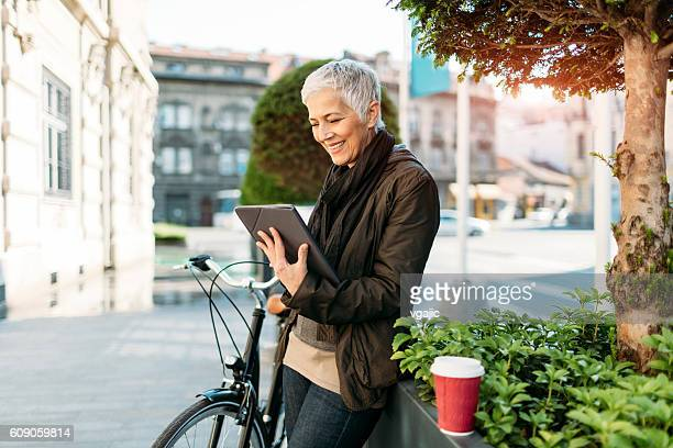 Mature Woman Using Digital Tablet Outdoors.