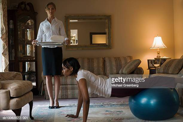 Mature woman using exercise ball, young maid waiting with mineral water on tray, in living room