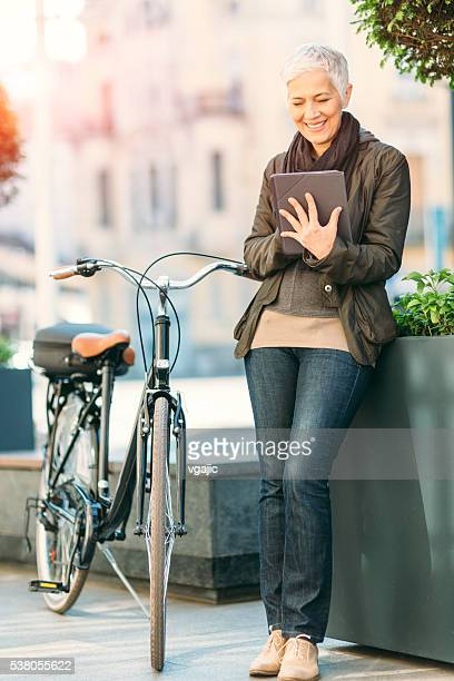Mature Woman Using Her Digital Tablet Outdoors.