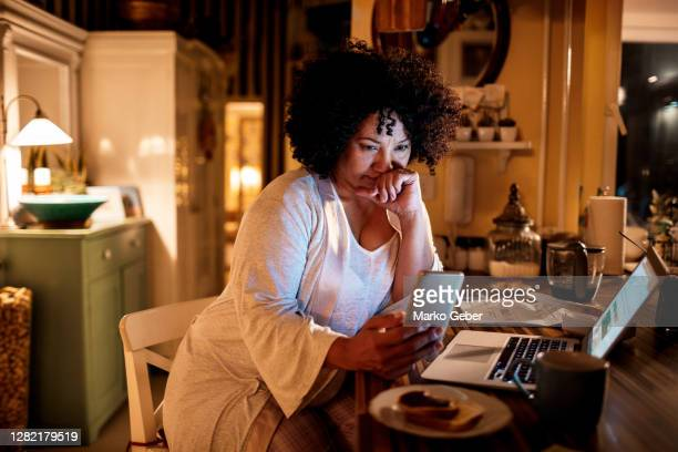 mature woman using her phone - worried stock pictures, royalty-free photos & images