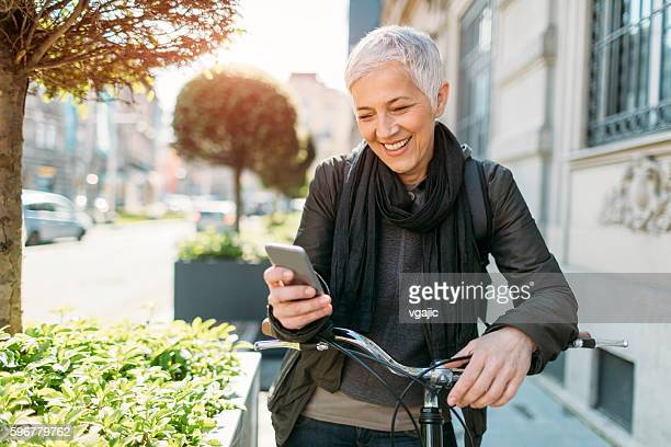 mature woman using her smart phone on bicycle. - white hair stock pictures, royalty-free photos & images