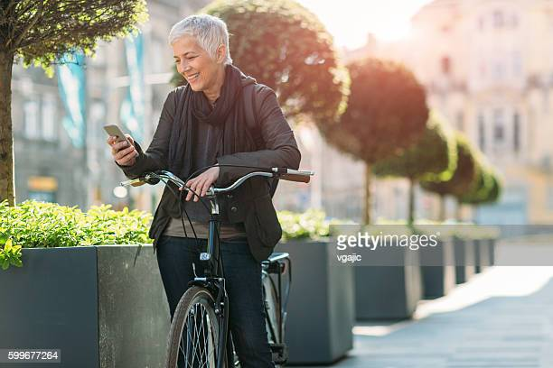 Ältere Frau benutzt Ihr Smartphone mit dem Fahrrad.