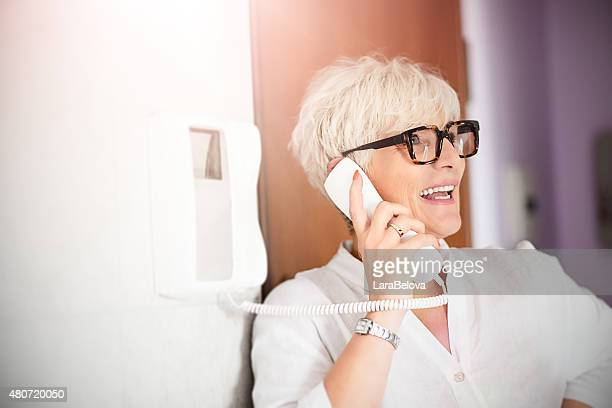 mature woman using interphone home - intercom stock pictures, royalty-free photos & images