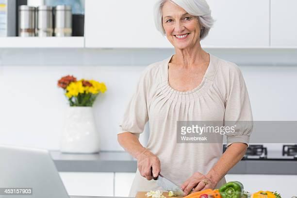 中年の女性のために野菜を使ったナイフ準備 - 根菜 ストックフォトと画像