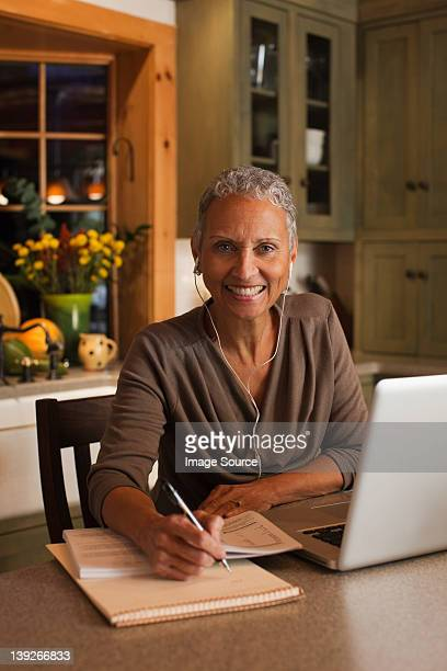 Mature woman using laptop and wearing ear phones, portrait