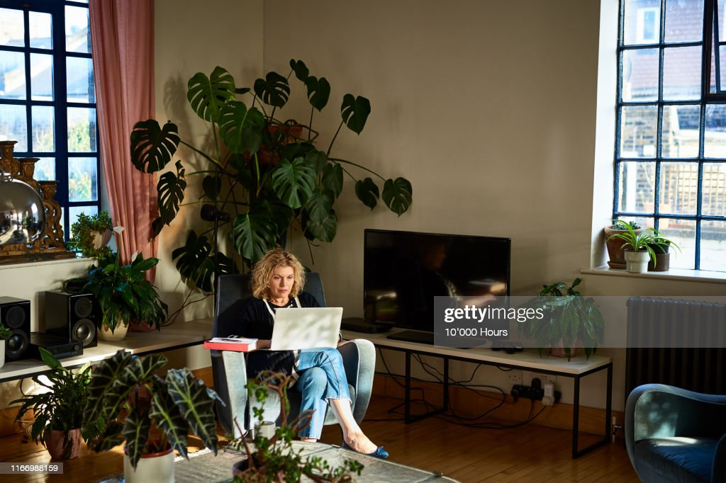 Mature woman using laptop in living room : Stock Photo
