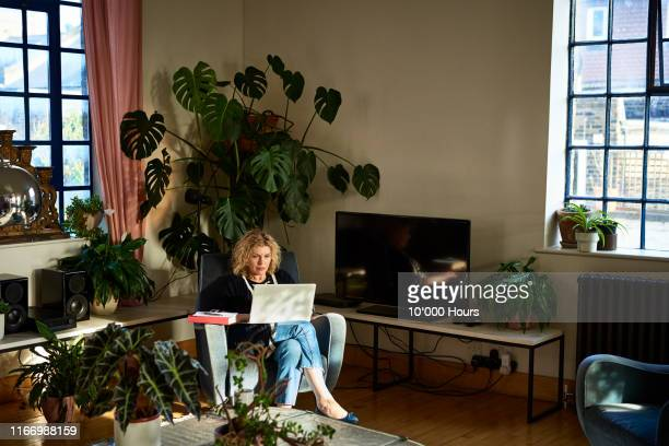 mature woman using laptop in living room - mature adult stock pictures, royalty-free photos & images