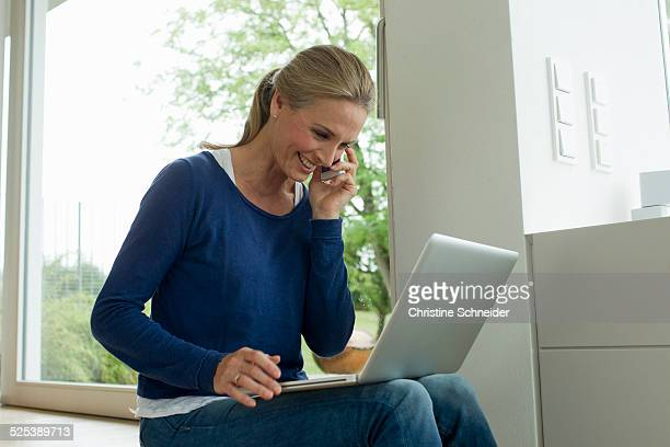 Mature woman using laptop on cell phone