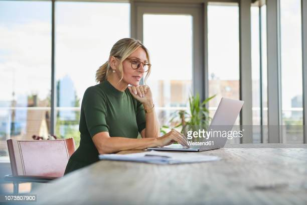 mature woman using laptop on table at home - red dress fotografías e imágenes de stock