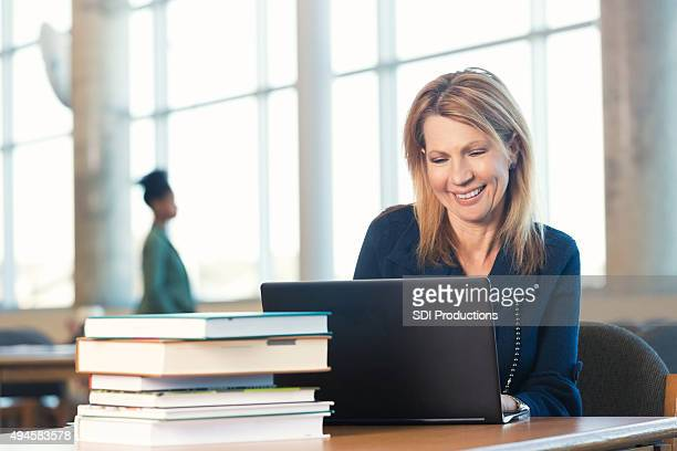 Mature woman using laptop, studying in modern library
