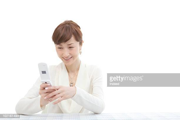 mature woman using mobile phone, smiling - 中年の女性一人 ストックフォトと画像