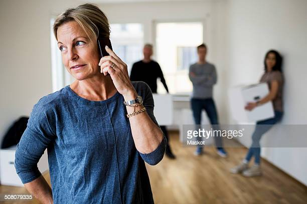 mature woman using mobile phone while family carrying moving boxes in background at home - mother in law stock pictures, royalty-free photos & images